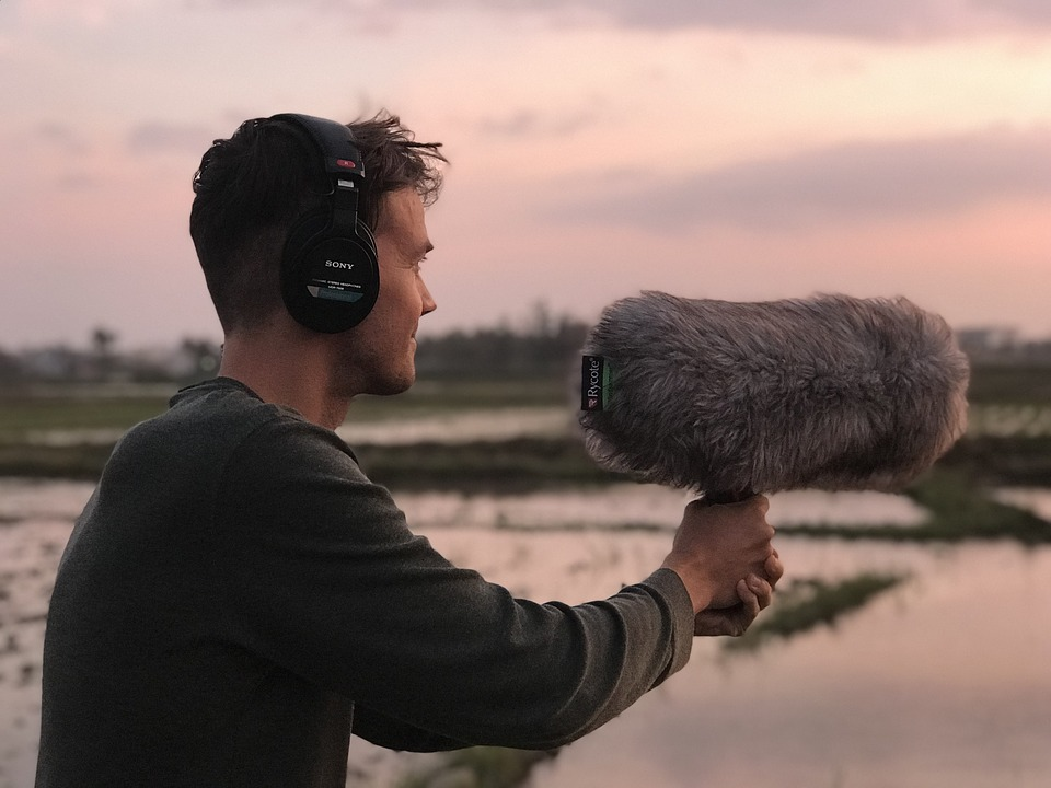 Man wearing headphones and holding a shotgun microphone in the wetlands.